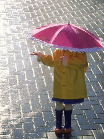 Tim Heneghan created this image of a child, hidden by her umbrella, checking the changing conditions. A passing summer rain has soak the pavement, and presumably all passersby, but now allows the sun to break through, shimmering brilliantly on the puddles below.