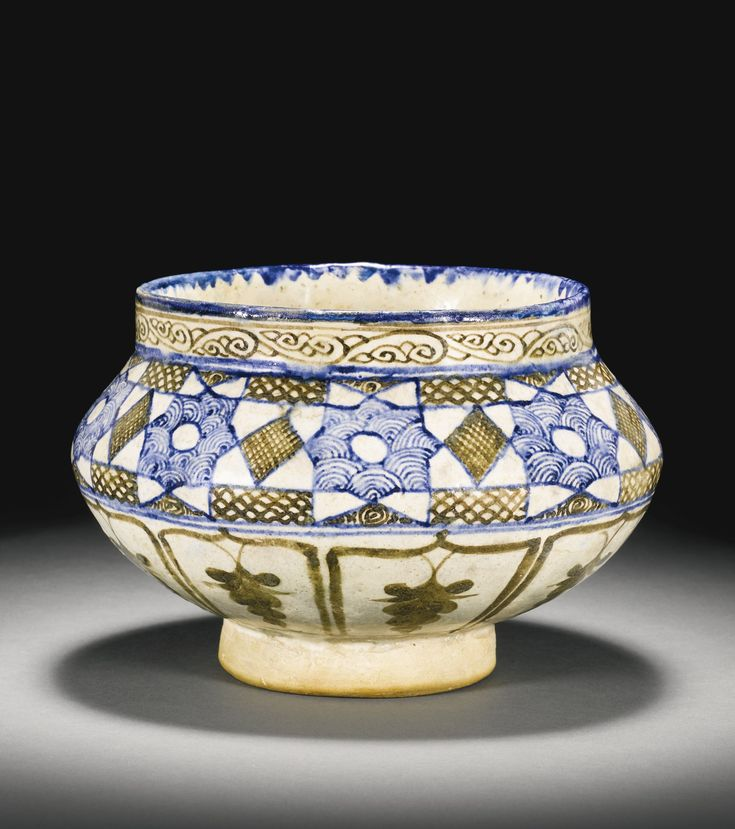 A Timurid or Mamluk blue, black and white bowl, Syria or Persia, 15th century the body of squat bulbous form on a short foot with a wide mouth with straight-edged rim, the exterior painted in cobalt blue and brown on an off-white ground, with a row of connecting eight-pointed stars containing wave-shape designs, between cross-hatched lozenge motifs, above painted brown arcades each containing a stylised grape-vine, the interior with a floral motif 14.8cm. height. 22cm. diam.