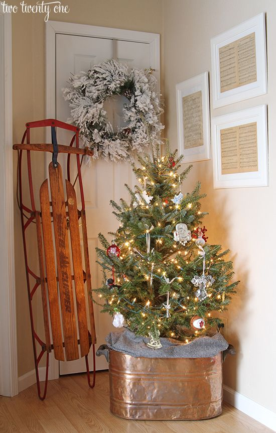 Classic Christmas entryway with a vintage sled, small tree with sentimental ornaments and copper boiler tree stand, and framed Christmas carol sheet music