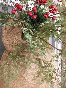 Christmas greenery in burlap...and tuck in a large grapevine wreath on on an old weathered board...