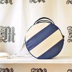 DotLine Classic / Beige×Kinariカラー ベージュ×かす入り生成りサイズ 24×11㎝(直径×マチ幅) 重さ 約260g ファスナー開き 30cm 肩紐 約160~90cm×3㎝(長さ×幅)組成 表地:綿100%(11号帆布) 裏地:ナイロン100% 肩紐:ポリエステル100%---------------帆布を配色につなぎ合わせ、円形のバッグに仕上げました。 おおきなドットの中にラインが走るデザイン。ななめ・よこ方向と、前・後面で各々ラインが異なります。マチ幅は大きく、500mlのペットボトルや長財布にポーチなどが、余裕を持って入るサイズ。裏地には、張りと硬さのあるナイロン生地を使用。内側にはパッチポケットが1つ。底部に縫い付けたテープが形状を安定させています。外側にはパスケースや携帯電話の出し入れに適したスラッシュポケット。切替を利用した隠しポケットになっています。 肩紐は取り外し可能で、金具で長さを調節できます。ハンドバッグとショルダーバッグの2WAY仕様です。[HOW TO WASH]軽い汚れは絞ったタオルなどで拭ってください。全体が...
