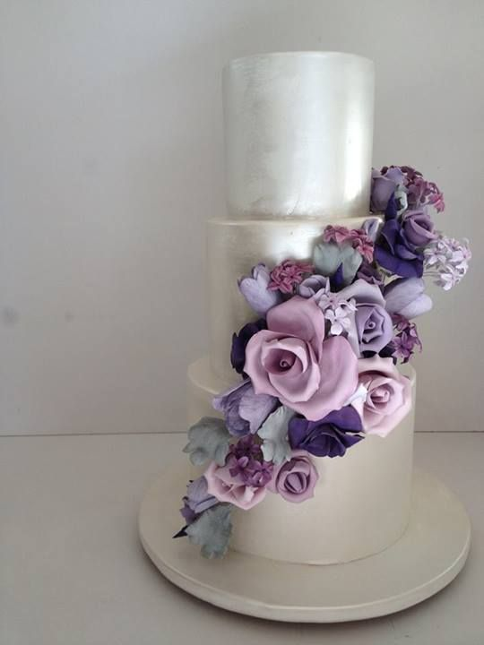 Lilac roses enhance a pearl white wedding cake / Cakesalouisa