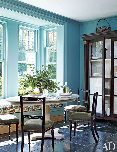 Miles Redd painted the breakfast area of a Connecticut house with a turquoise-blue by Farrow & Ball. The chairs are antique, and the window seat's cushion fabric is by Bennison.