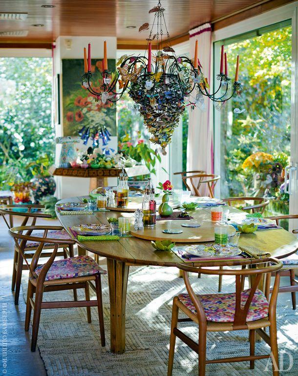 Столовая. Кованая люстра украшена бабочками из ткани. Стол по дизайну Бруно Матссона, стулья Wishbone Ханса Вегнера; подушки иковер, Missoni Home.