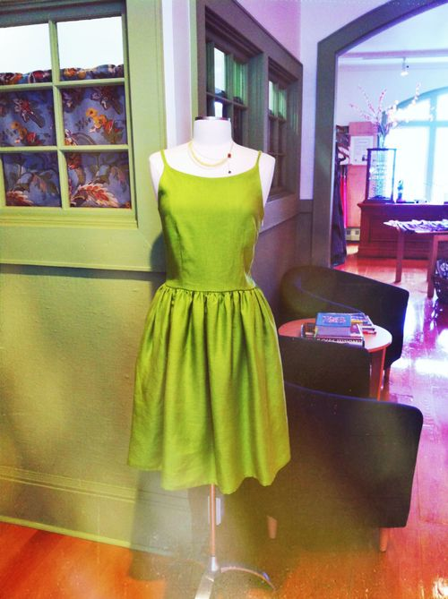 Green linen sundress in a classic style. By Terra Cotta Clothing $164  Paired with woven sandals or wedges this dress is perfect for a summer date on the boardwalk. Add a lightweight blazer and wear it to the office, or dress it up and wear it to a white church wedding.