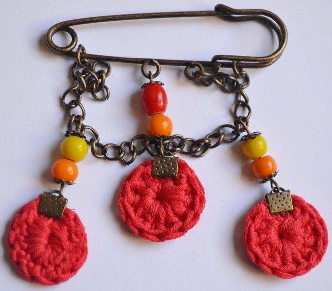 Prendedor hecho a mano combinando tejido al crochet y piedras de vidrio.