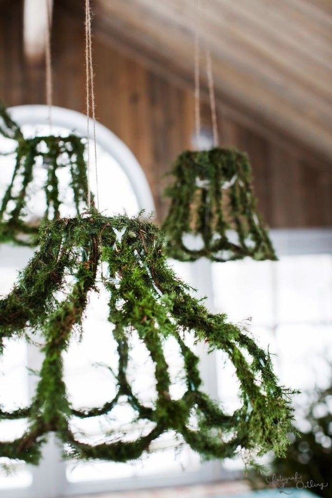 Tendrils of delicate evergreen wrapped around the spokes of a chandelier add a breath of fresh air.