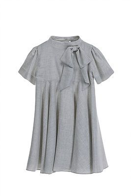Crepe Dress with Bow – Light Grey. An effortlessly elegant dress, with an empire line cut, in a light grey. There is a large, detachable bow at the front set to the side, with short sleeves, and 5 buttons at the rear for fastening. Simple but always refined. 85% Viscose, 15% Cotton. Lining: 100% Polyester. Gentle Dry Clean only.