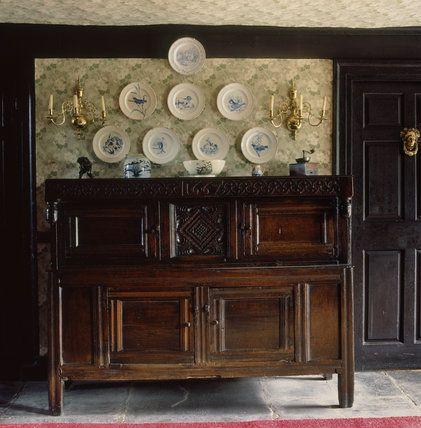A local carved oak press cupboard at Hill Top House, bought by Beatrix at a local farm sale, above which hang eight plates painted with animals and birds by her father, Rupert. Near Sawrey, Cumbria, England, UK