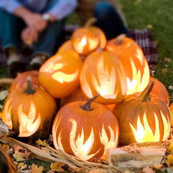 Pumpkin Bonfire  If you have a little more time, you'll have fun pulling together this cool carving idea. Add the bonfire centerpiece to a backyard table or use it as a focal point in front. You'll need about 10 to 12 pumpkins and flickering candles to make these flames come to life.