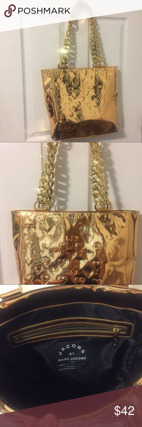 Marc Jacobs gold shoulder bag In great condition, metallic gold with logo. Gold plastic chain link detail, drop is approx. 12 inches. Black interior with zippered side pocket. Measures 12 wide by 13 high. Marc By Marc Jacobs Bags Shoulder Bags