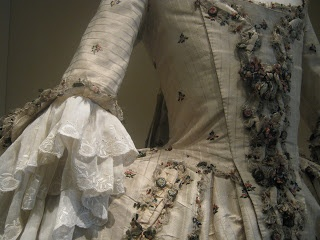 Resplendent in its glass cabinet at the Leeds City Museum, this 18th century gown is in wonderful condition. Just look at that white lace.