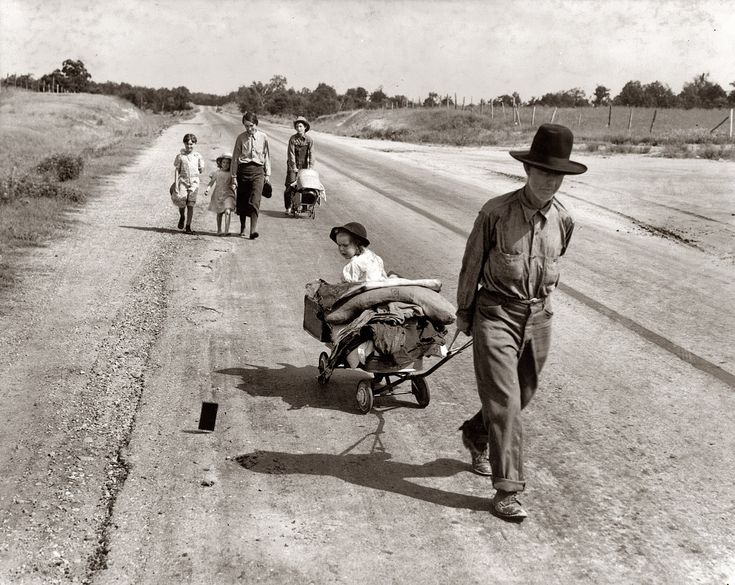 "June 1938. Pittsburg County, Oklahoma. ""Family walking on highway, five children. Started from Idabel, bound for Krebs. In 1936 the father farmed on thirds and fourths at Eagleton, McCurtain County. Was taken sick with pneumonia and lost farm. Was refused relief in county of 15 years' residence because of temporary residence elsewhere."" Still, they didn't give up... they were Americans. The child is looking at what is probably the exposure sheet from the camera blown away. Pic by Dorothea…"