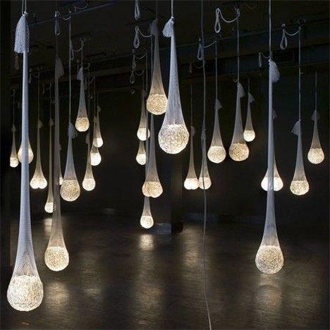 Mit Wasser und Leuchtstäben gefüllte weiße Ballons, die mit Hilfe von Netz, Chiffon oder Tüll an der Decke befestigt werden