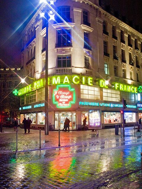 The neon lights of the Pharmacie de France are reflected on the wet pavements.  Taken last weekend on a visit to Lille in Northern France.   http://parapharmacie-en-ligne.blogspot.co.at/2013/08/le-bien-etre-absolu-avec-viveo-la.html