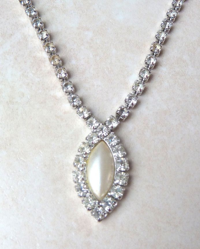 Stunning vintage rhinestone necklace with large faux pearl by vintage designer Sarah Coventry. The necklace is detailed with beautifully shimmering clear rhinestones throughout its entire length with a central faux pearl drop edged by rhinestones. Signed with copyright symbol and Sarah Cov to the back of the clasp.