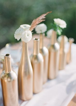 Gold wedding centerpieces made from spray painted wine bottles via Every Last Detail.