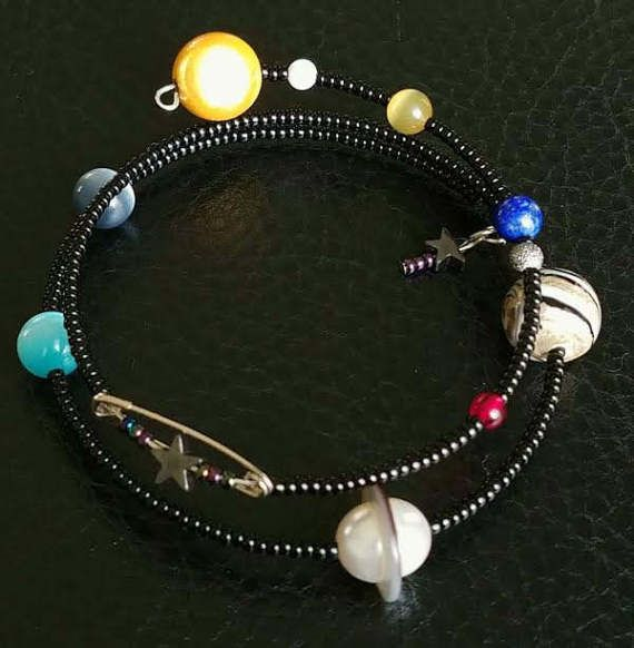 Spiral memory wire bracelet shows our solar system with its nine planets and the sun. Beautiful gift for any pro-science activist or geek. My favorite part is the sun bead, a Japanese Miracle bead which actually glows! The planetary beads are a bit scarce but were making as many of them as the can. Stay tuned. Proceeds will benefit Earth Justice, cuz that little blue ball is kind of important to us. www.earthjustice.org  Today's environmental challenges are greater than ever. But we live in…