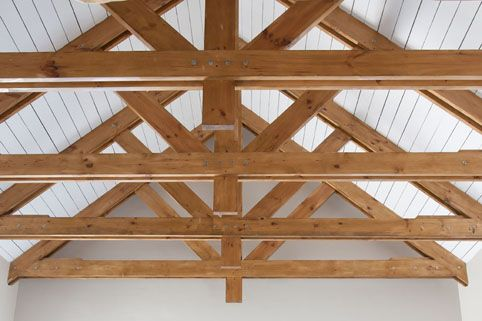 Natural wood trusses offset against contrasting roofing material