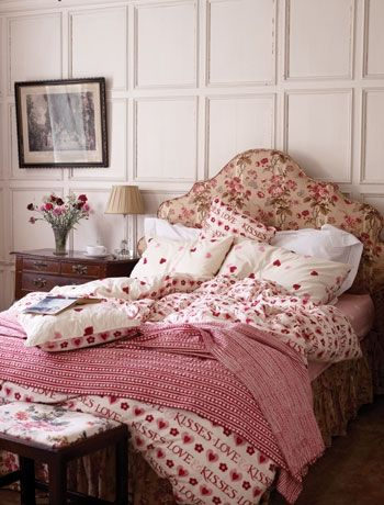 Create a typically British country home style bedroom by using simple patterns, traditional furniture and sensible colours! This room is a great example of how the British decorate - a cornucopia of colour, pattern and style in the same hues and colours that we somehow get away with even though there is an element of mis-match! Pink hearts bedlinen from Emma Bridgewater.