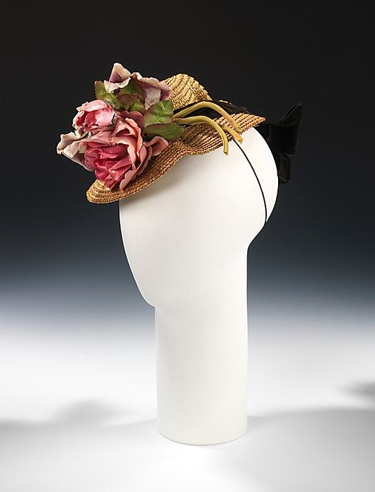 Straw doll hat with silk flowers and black velvet ribbon, by Sally Victor, American, 1937. A virtuoso of manipulating common millinery materials such as straw into new and interesting styles, Victor expertly pleats and folds one piece of chartreuse straw into this stylish creation. On most doll hats, the focus is on the front, but Victor balances the look by extending the velvet ribbon to the back, ending in an oversized feminine bow.