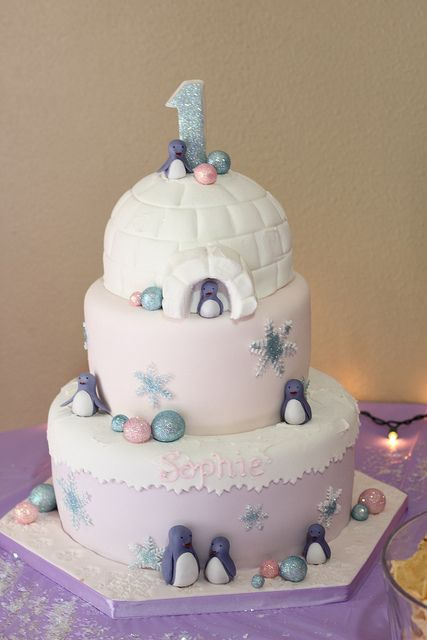 Igloo cake with penguins for first birthday. We can help achieve this look by checking out our website for cake dummies, cake boards and cupcake stands!