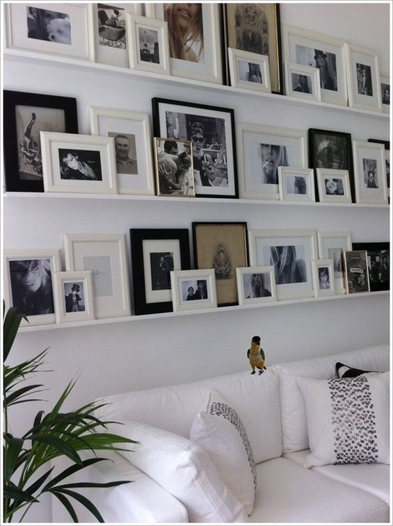 Photo memory wall with black and white frames on white shelves