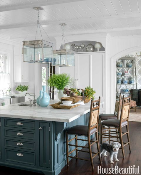 Farrow & Ball's Down Pipe on the island cabinetry grounds the otherwise all-white kitchen. Pendant lights, the Urban Electric Co.