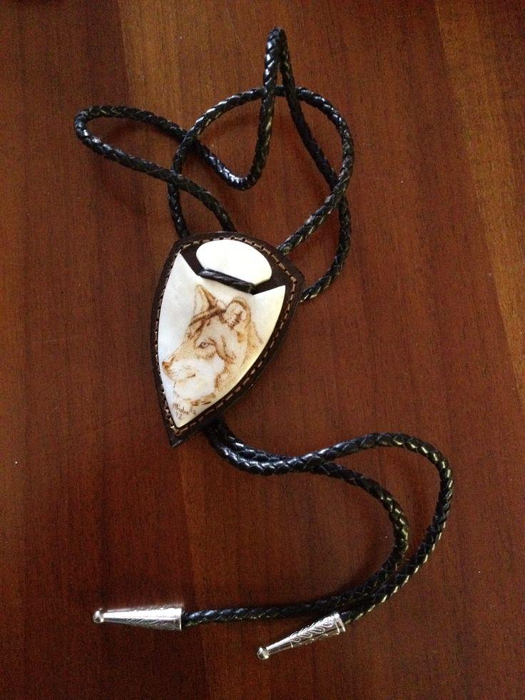 Bolo tie, realizzato in osso di bue applicata su placca di cuoio. Eseguito e cucito a mano. Pirografia su osso rappresentante un lupo dell'Alaska.