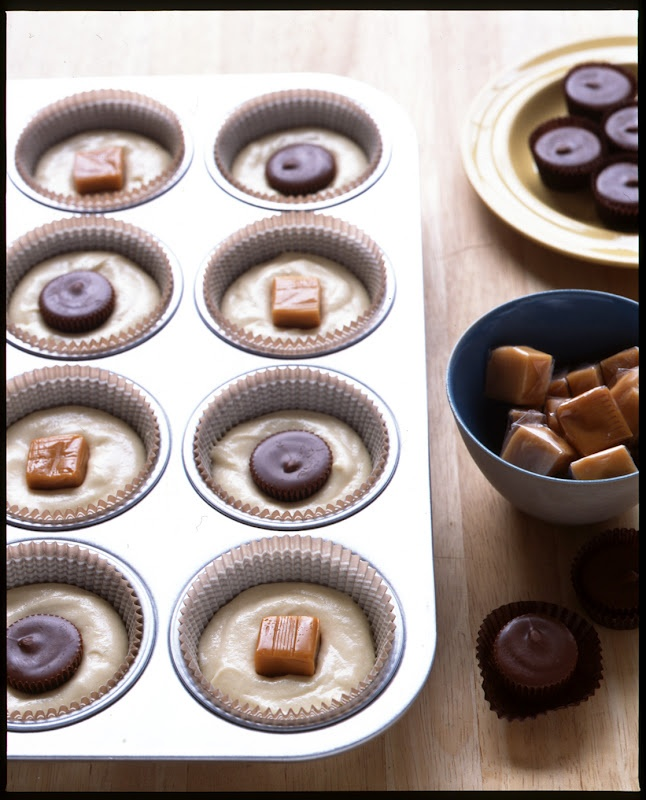 Add candy pieces to the centers of cupcakes. Fill liners half way with batter then drop in your favorite candies. Cover with remaining batter and bake as usual