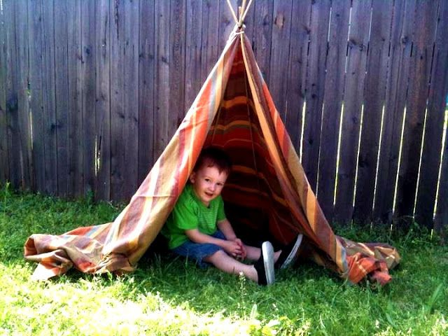 EZ Cheapo teepee: they used some bamboo poles they bought at Wal-Mart in the garden section (only $1.50 for a package of 12) as the basic structure. Pushed them into the ground, tied them together at the top with some rope, draped a fun looking table cloth over the top, and tied it to the sides. Instant tepee!