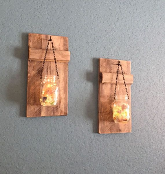 This listing is for beautiful rustic mason jar holders that hang from the holder with battery operated L.E.D. firefly lights. They are made from reclaimed wood and are stained. The mason jars each have a personality unique to themselves, containing sea shells and sea glass. You may order with firefly lights or without firefly lights. Each of these carefully hand-crafted candle holders will have unique characteristics. They will have cracks, holes, knots and color variations all unique to…