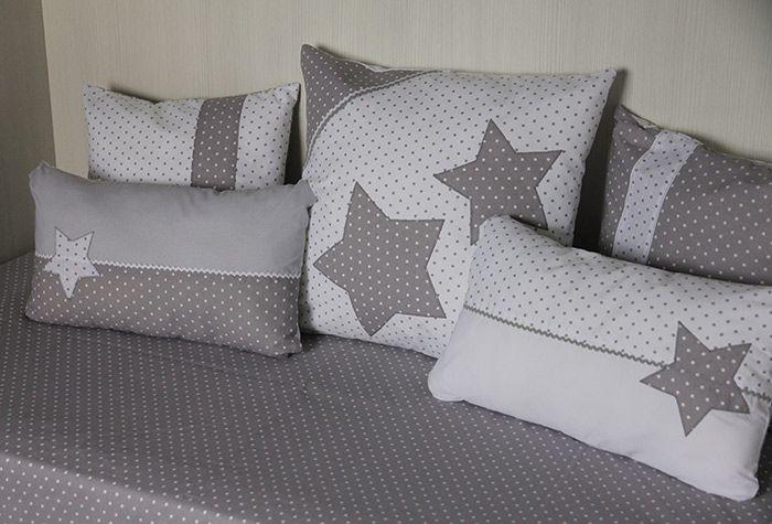 Conjunto de cama en gris. Funda nórdica reversible con cierre de snaps. Cojines de tres tamaños diferentes con estrellas bordadas.