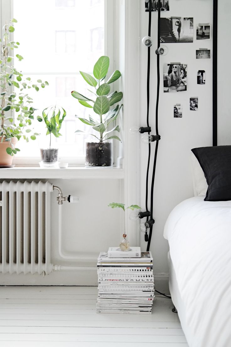 skandinavian bedroom w/ magazine stack instead of bedside table, plants, photos | #bed #white