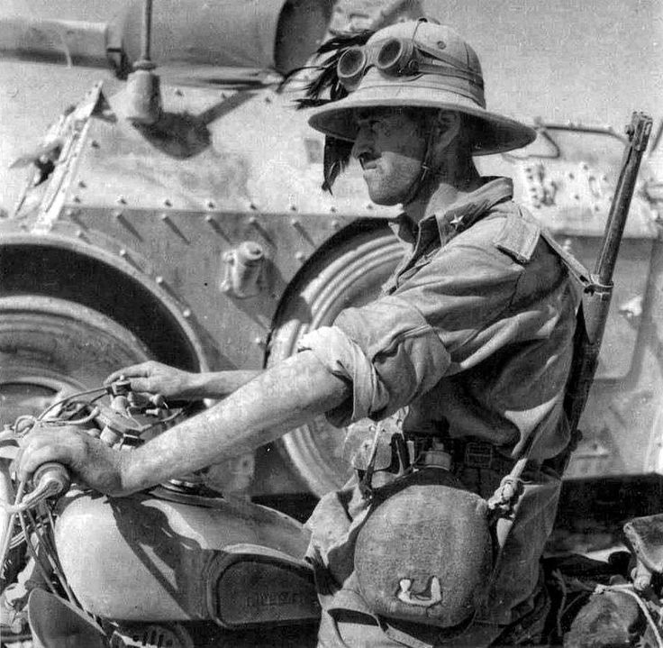 A dispatch rider on his Moto Guzzi advancing beside a Autoblinda AB41 armored car in North Africa during 1941