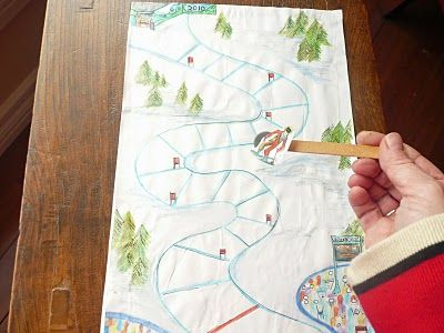 Make Olympic venues (this one is a downhill skier but we could choose summer sports) on cardboard and athletes that you move with magnets!  From That Artist Woman.