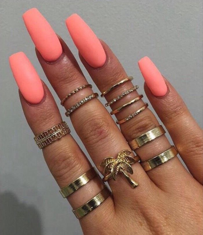neon peach pink nail polish, on long coffin nails, attached to a tan hand, with …