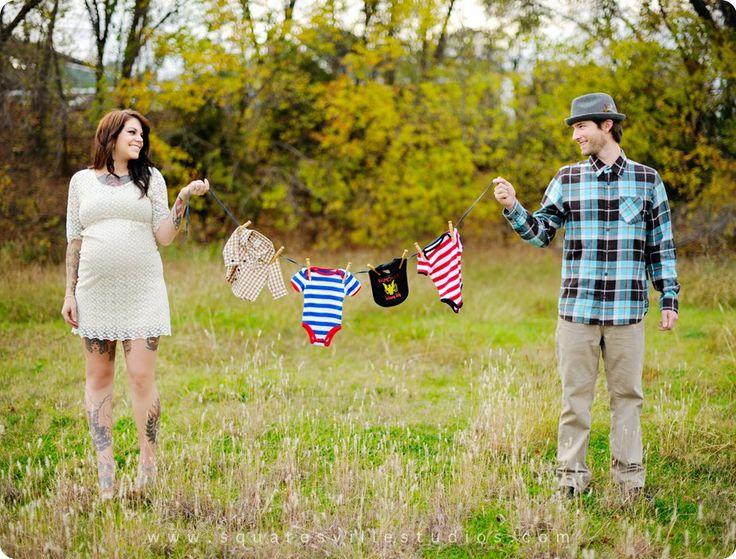 Sesión de fotos de maternidad pareja sosteniendo la ropa del bebé