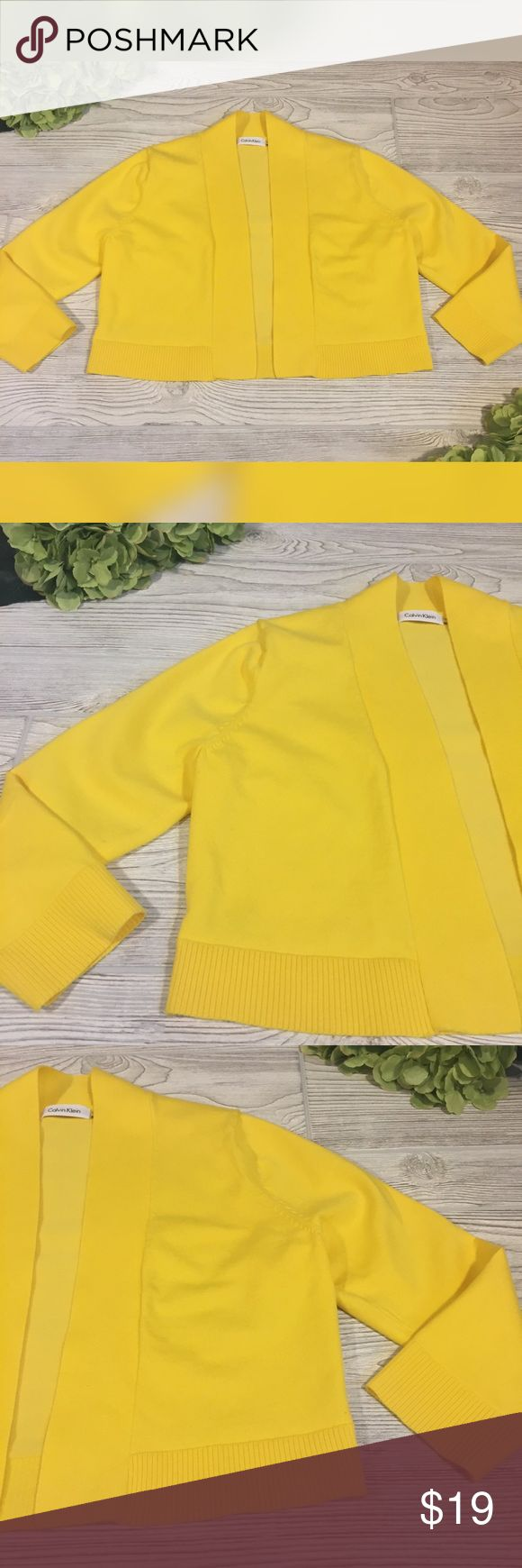 """Calvin Klein Yellow Cropped Shrug Adorable little yellow Calvin Klein shrug in excellent condition. Cropped. 3/4 length sleeves. Approximate flat measurements are armpit to armpit 17.5"""", hem opening 18.5"""", and shoulder to hem length is 16.5"""". Happy to answer questions! Calvin Klein Sweaters Shrugs & Ponchos"""