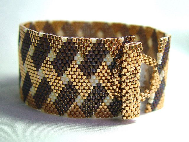 "This cuff was created with matte chocolate brown AB, opaque cream AB and metallic gold Delicas in a ""weave"" pattern. After I started it, I thought it look rich and decadent...then I thought it looked like S'mores!"