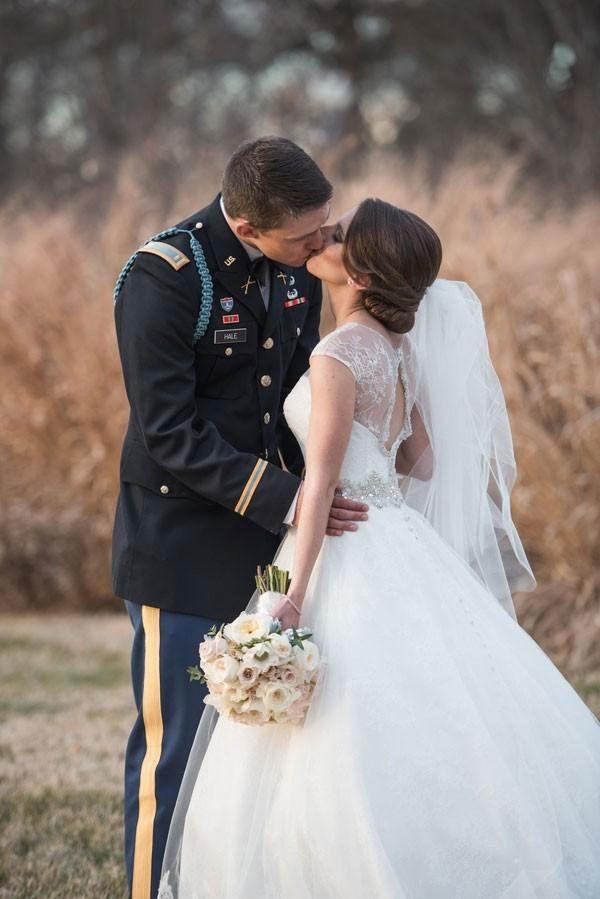 Military groom kisses bride in princess wedding dress.
