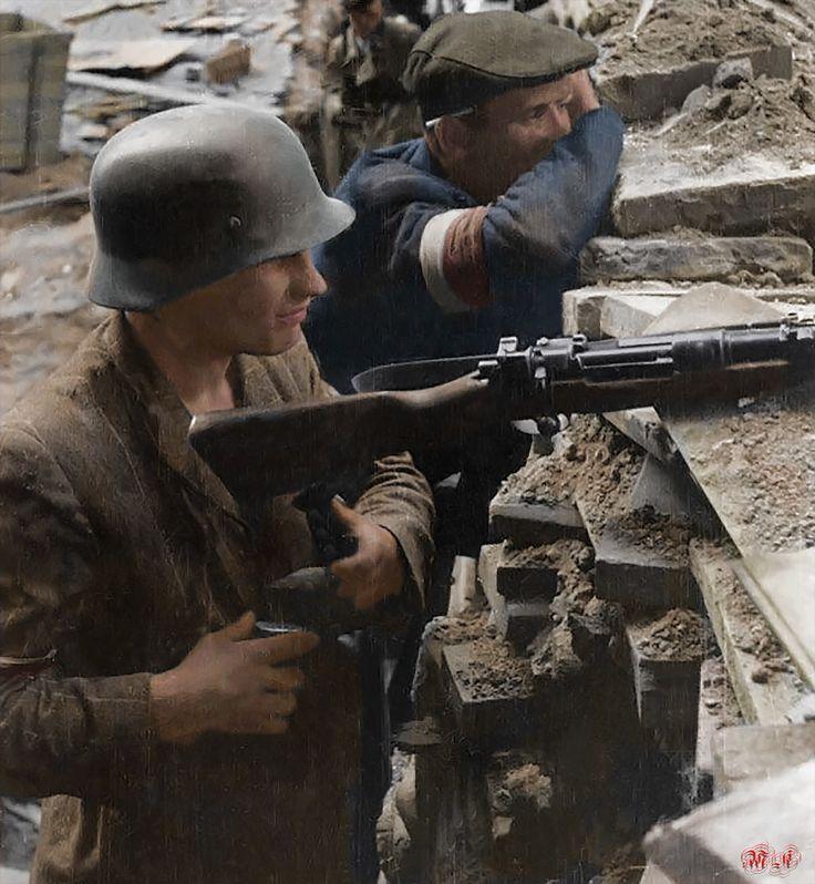 Śródmieście Północne. Powstańcy na barykadzie obserwujący przedpole budynków PAST-y przy ulicy Zielnej 37/39. Ujęcie z bramy kamienicy nr 30. Na pierwszym planie gotowy do strzału karabin Mauser wz. 1898k Zrodło : MPW