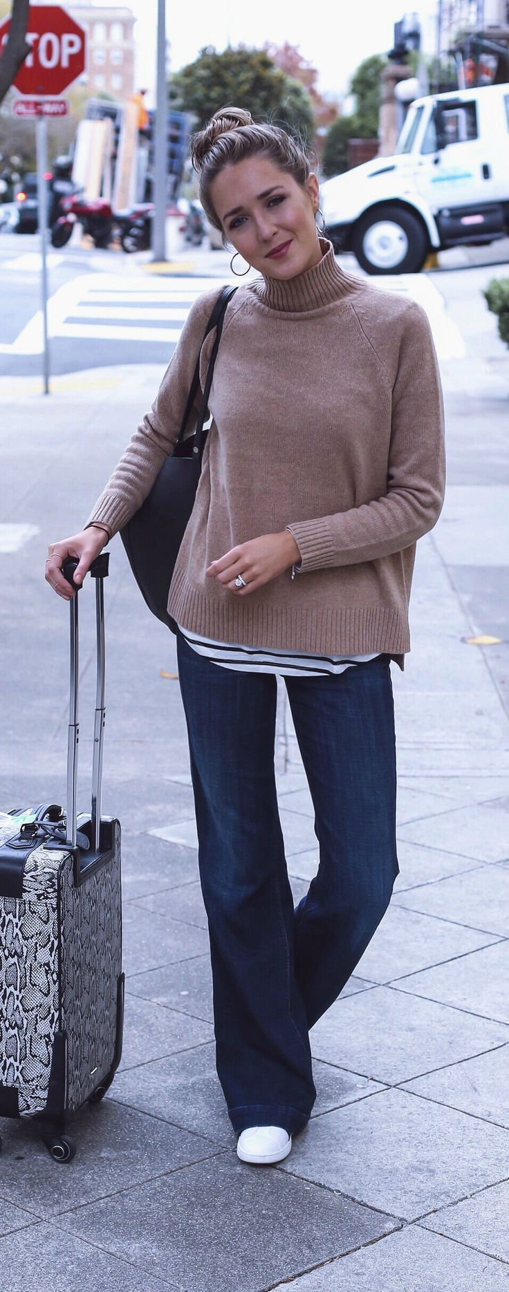 #travelstyle camel turtleneck chunky tunic sweater, layered over black and white striped long t-shirt, wide leg flare jeans, sneakers, hoop earrings