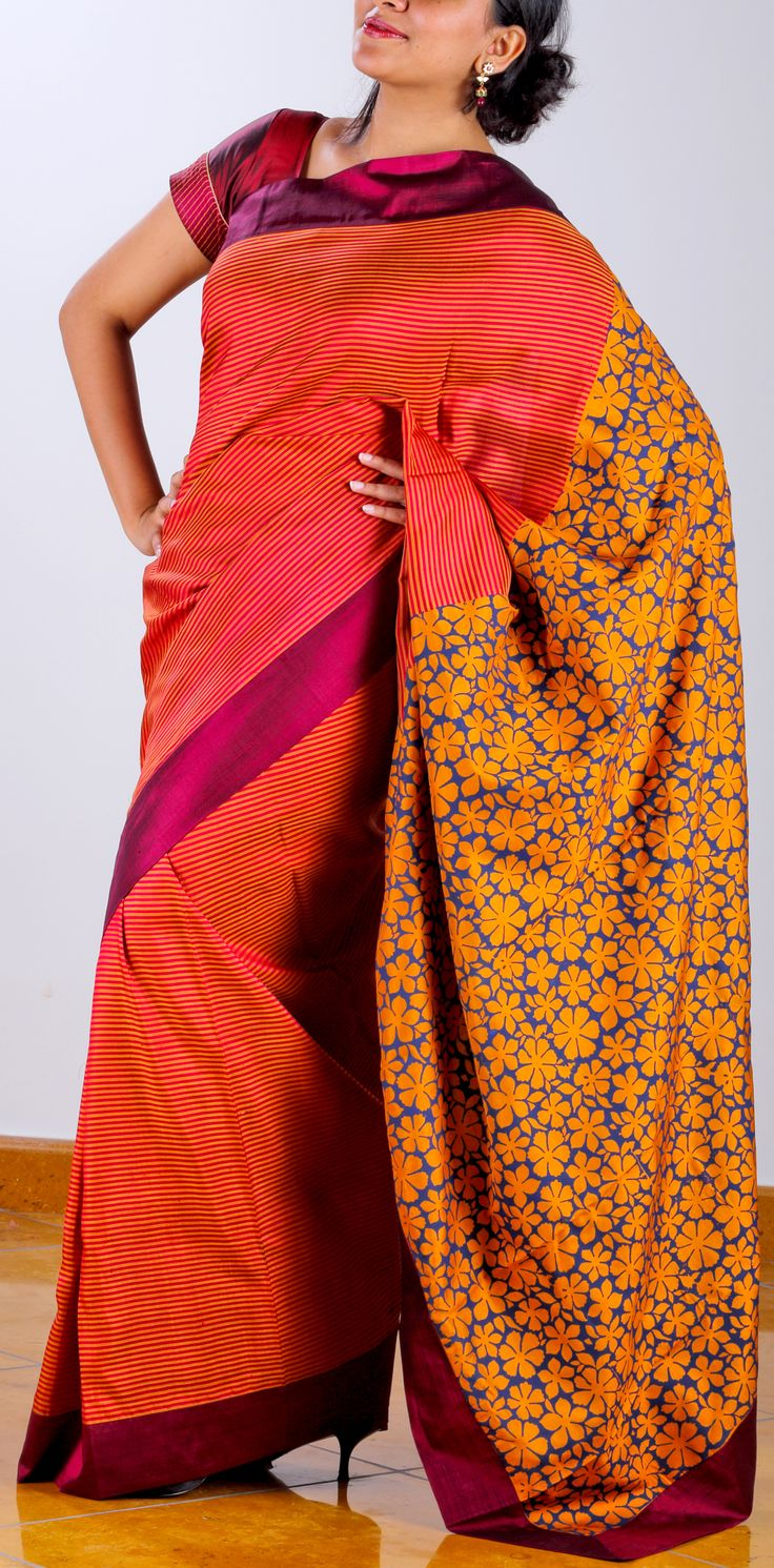 A mirage in orange? This double shaded Kanchipuram saree with bold red stripes, enhanced with a maroon border is a true riot of colours and designs with its unexpected mustard floral pallu! This printing technique is called 'gadh' or negative printing where the surrounding part of the flowers is filled with color. SHOP AT www.ubikaa.com