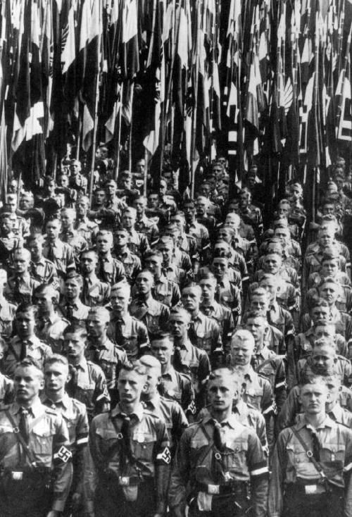 thevirussickness Hitler Youth with standards at a Nazi party rally in Nuremberg.