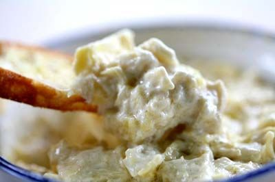 Quick and easy, hot artichoke dip with artichoke hearts, Parmesan cheese, mayonnaise, and salt and pepper.