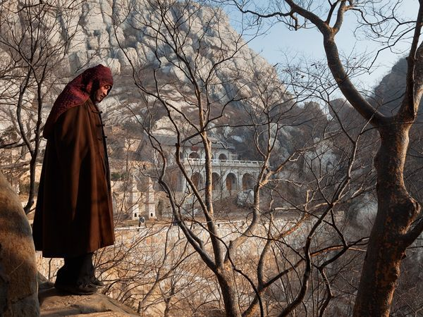 Buddhist monk and kung fu master Shi Dejian (above) and his disciples hauled bags of cement and roof tiles up steep mountain paths to build an isolated retreat (in background) away from the tourist crowds at the Shaolin Temple. Photograph by Fritz Hoffmann, National Geographic