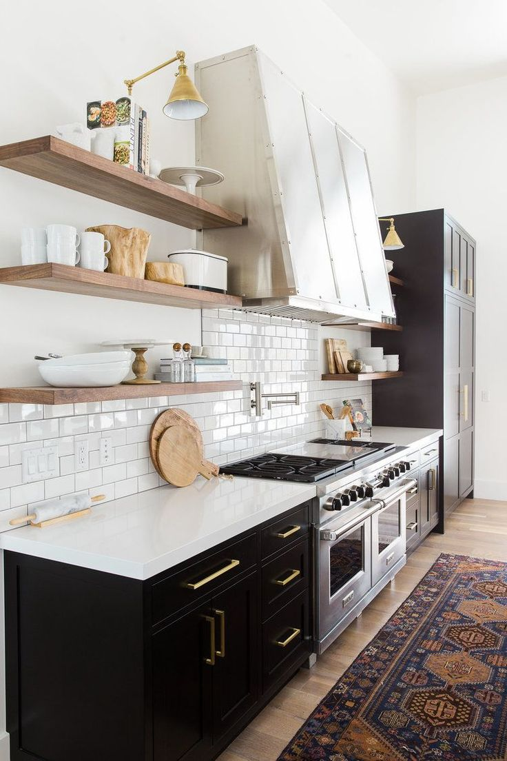 love the ligthing above the open shelves. Statement range hood and black cabinetry. vintage rug in the kitchen. Designed by Studio McGee