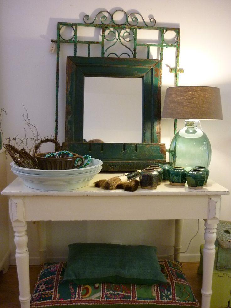 Interieur in groen: oude keukentafel, glazen lampvoet, oude gemberpotjes, oude Indiase spiegel, oud ijzeren hekje.