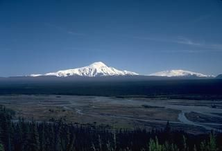 This view, across the Copper River to the SE, shows 4949-m-high Mount Sanford (left) and 4317-m-high Mount Wrangell (right), two massive andesitic shield volcanoes. The dissected Sanford shield volcano has a broad, bulbous top that is surrounded by steep-walled glacial cirques. Most of the volcano formed in the Pleistocene, but part of the summit region may be of Holocene age. Eruptive activity at the younger, less-dissected Wrangell volcano has continued into historical time.
